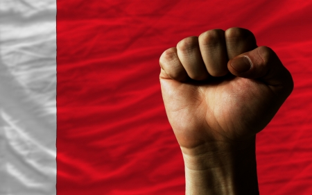 complete national flag of bahrain covers whole frame, waved, crunched and very natural looking. In front plan is clenched fist symbolizing determination Stock Photo - 13953460