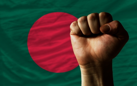 bangladesh: complete national flag of bangladesh covers whole frame, waved, crunched and very natural looking. In front plan is clenched fist symbolizing determination Stock Photo