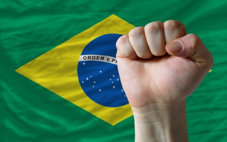 determinism: complete national flag of brazil covers whole frame, waved, crunched and very natural looking. In front plan is clenched fist symbolizing determination
