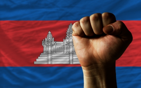 determinism: complete national flag of cambodia covers whole frame, waved, crunched and very natural looking. In front plan is clenched fist symbolizing determination