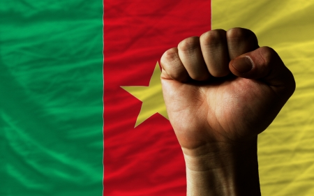 determinism: complete national flag of cameroon covers whole frame, waved, crunched and very natural looking. In front plan is clenched fist symbolizing determination