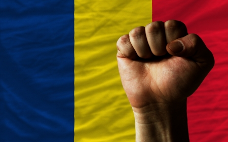 chadian: complete national flag of chad covers whole frame, waved, crunched and very natural looking. In front plan is clenched fist symbolizing determination