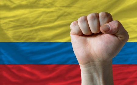 determinism: complete national flag of colombia covers whole frame, waved, crunched and very natural looking. In front plan is clenched fist symbolizing determination