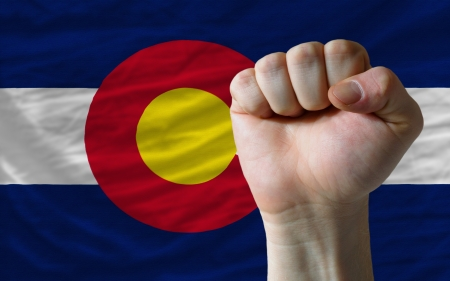 complete american state of colorado covers whole frame, waved, crunched and very natural looking. In front plan is clenched fist symbolizing determination photo