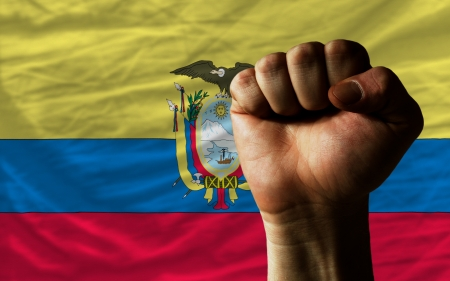 determinism: complete national flag of ecuador covers whole frame, waved, crunched and very natural looking. In front plan is clenched fist symbolizing determination Stock Photo