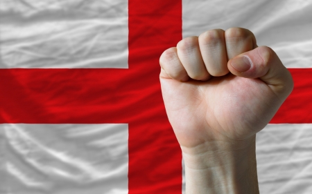 determinism: complete national flag of england covers whole frame, waved, crunched and very natural looking. In front plan is clenched fist symbolizing determination