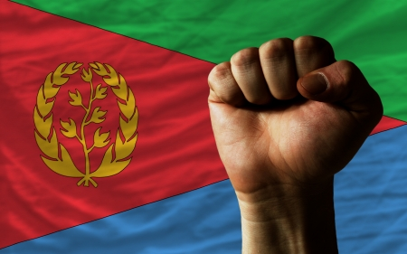 determinism: complete national flag of eritrea covers whole frame, waved, crunched and very natural looking. In front plan is clenched fist symbolizing determination
