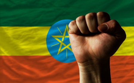 determinism: complete national flag of ethiopia covers whole frame, waved, crunched and very natural looking. In front plan is clenched fist symbolizing determination Stock Photo