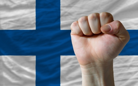 complete finland national flag covers whole frame, waved, crunched and very natural looking. In front plan is clenched fist symbolizing determination photo
