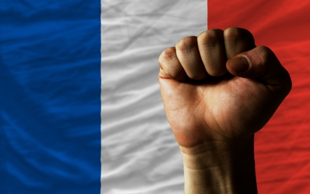 complete national flag of france covers whole frame, waved, crunched and very natural looking. In front plan is clenched fist symbolizing determination photo