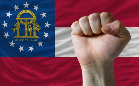 determinism: complete american state of georgia flag covers whole frame, waved, crunched and very natural looking. In front plan is clenched fist symbolizing determination