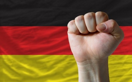 determinism: complete national flag of germany covers whole frame, waved, crunched and very natural looking. In front plan is clenched fist symbolizing determination