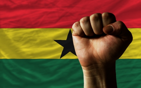 determinism: complete national flag of ghana covers whole frame, waved, crunched and very natural looking. In front plan is clenched fist symbolizing determination Stock Photo
