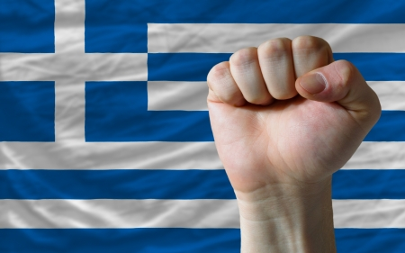 determinism: complete national flag of greece covers whole frame, waved, crunched and very natural looking. In front plan is clenched fist symbolizing determination