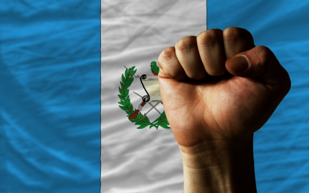 complete national flag of guatemala covers whole frame, waved, crunched and very natural looking. In front plan is clenched fist symbolizing determination photo