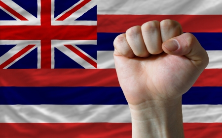determinism: complete american state of hawaii flag covers whole frame, waved, crunched and very natural looking. In front plan is clenched fist symbolizing determination