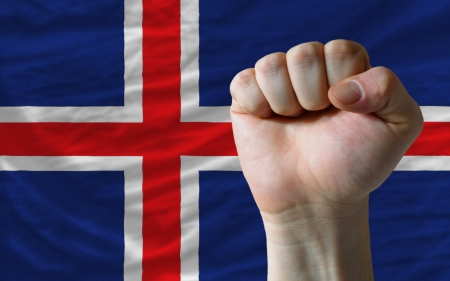 determinism: complete national flag of iceland covers whole frame, waved, crunched and very natural looking. In front plan is clenched fist symbolizing determination Stock Photo