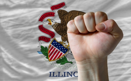 determinism: complete american state of illinois flag covers whole frame, waved, crunched and very natural looking. In front plan is clenched fist symbolizing determination Stock Photo