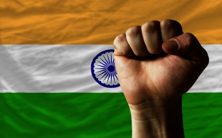 determinism: complete national flag of india covers whole frame, waved, crunched and very natural looking. In front plan is clenched fist symbolizing determination