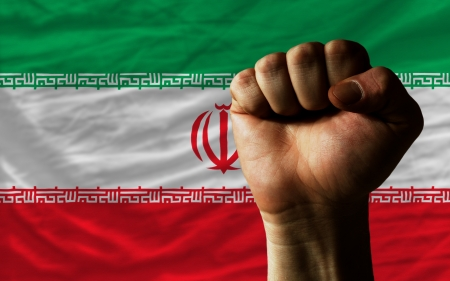 determinism: complete national flag of iran covers whole frame, waved, crunched and very natural looking. In front plan is clenched fist symbolizing determination Stock Photo