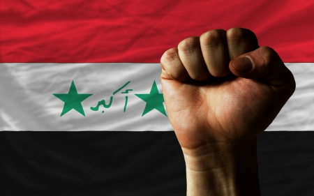 determinism: complete national flag of iraq covers whole frame, waved, crunched and very natural looking. In front plan is clenched fist symbolizing determination
