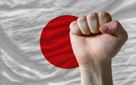 complete national flag of japan covers whole frame, waved, crunched and very natural looking. In front plan is clenched fist symbolizing determination photo