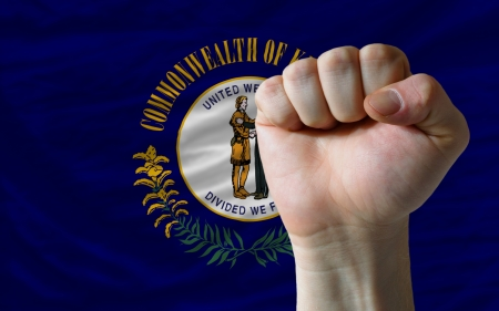 determinism: complete american state of kentucky flag covers whole frame, waved, crunched and very natural looking. In front plan is clenched fist symbolizing determination Stock Photo