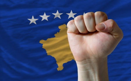 determinism: complete national flag of kosovo covers whole frame, waved, crunched and very natural looking. In front plan is clenched fist symbolizing determination