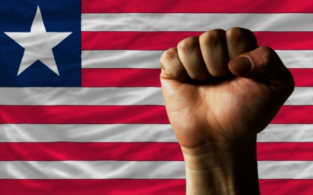 nationalism: complete national flag of liberia covers whole frame, waved, crunched and very natural looking. In front plan is clenched fist symbolizing determination