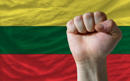 determinism: complete national flag of lithuania covers whole frame, waved, crunched and very natural looking. In front plan is clenched fist symbolizing determination