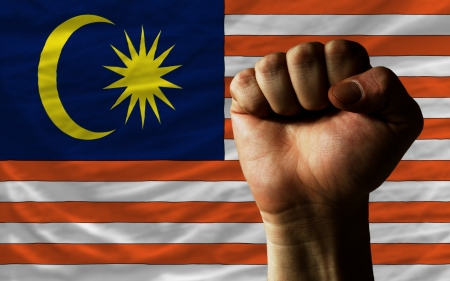determinism: complete national flag of malaysia covers whole frame, waved, crunched and very natural looking. In front plan is clenched fist symbolizing determination Stock Photo