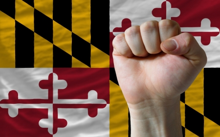 maryland flag: complete american state of maryland flag covers whole frame, waved, crunched and very natural looking. In front plan is clenched fist symbolizing determination Stock Photo