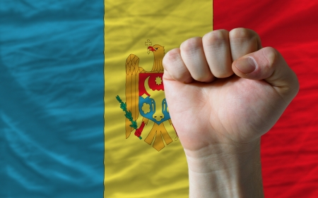complete national flag of moldova covers whole frame, waved, crunched and very natural looking. In front plan is clenched fist symbolizing determination photo