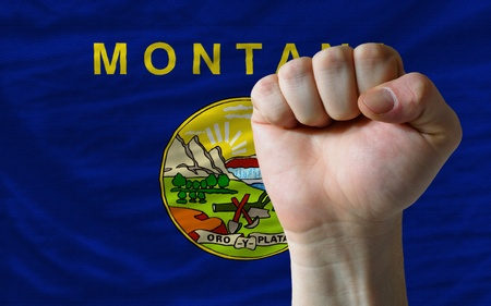 determinism: complete american state of montana covers whole frame, waved, crunched and very natural looking. In front plan is clenched fist symbolizing determination Stock Photo