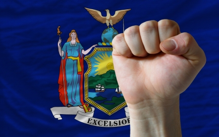 determinism: complete american state of new york covers whole frame, waved, crunched and very natural looking. In front plan is clenched fist symbolizing determination