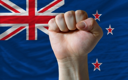determinism: complete national flag of new zealand covers whole frame, waved, crunched and very natural looking. In front plan is clenched fist symbolizing determination