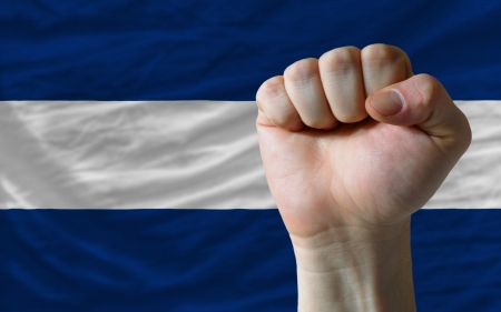 complete national flag of nicaragua covers whole frame, waved, crunched and very natural looking. In front plan is clenched fist symbolizing determination photo