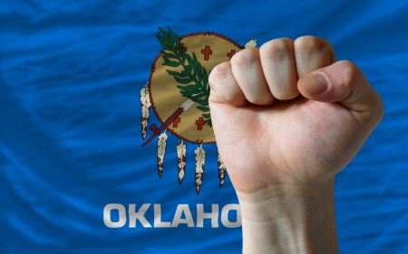 determinism: complete american state of oklahoma covers whole frame, waved, crunched and very natural looking. In front plan is clenched fist symbolizing determination