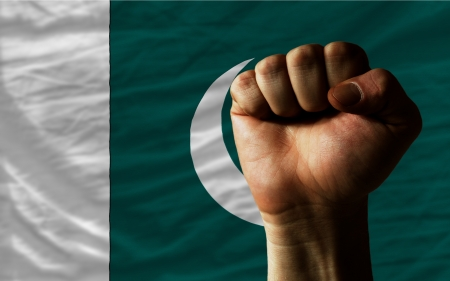 determinism: complete national flag of pakistan covers whole frame, waved, crunched and very natural looking. In front plan is clenched fist symbolizing determination