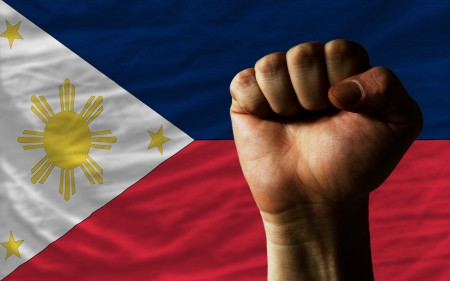 reluctant: complete national flag of philippines covers whole frame, waved, crunched and very natural looking. In front plan is clenched fist symbolizing determination