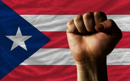 puertorico: complete national flag of puertorico covers whole frame, waved, crunched and very natural looking. In front plan is clenched fist symbolizing determination Stock Photo