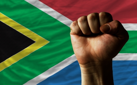 determinism: complete national flag of south africa covers whole frame, waved, crunched and very natural looking. In front plan is clenched fist symbolizing determination