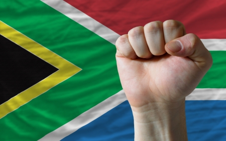 complete national flag of south africa covers whole frame, waved, crunched and very natural looking. In front plan is clenched fist symbolizing determination photo