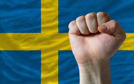 complete national flag of sweden covers whole frame, waved, crunched and very natural looking. In front plan is clenched fist symbolizing determination photo