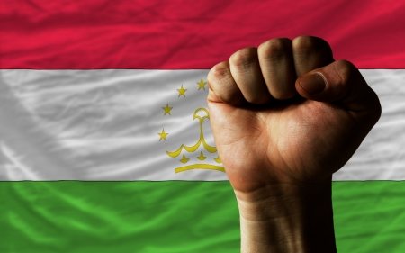 determinism: complete national flag of tajikistan covers whole frame, waved, crunched and very natural looking. In front plan is clenched fist symbolizing determination Stock Photo