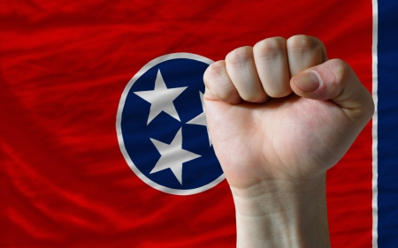 determinism: complete american state of tennessee covers whole frame, waved, crunched and very natural looking. In front plan is clenched fist symbolizing determination Stock Photo