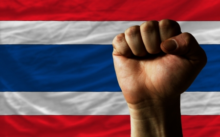 complete national flag of thailand covers whole frame, waved, crunched and very natural looking. In front plan is clenched fist symbolizing determination photo