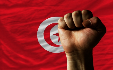 complete national flag of tunisia covers whole frame, waved, crunched and very natural looking. In front plan is clenched fist symbolizing determination photo