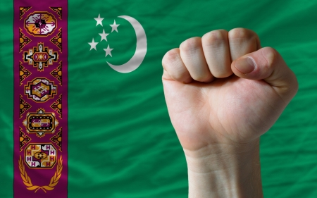 determinism: complete national flag of turkmenistan covers whole frame, waved, crunched and very natural looking. In front plan is clenched fist symbolizing determination