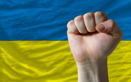 complete national flag of ukraine covers whole frame, waved, crunched and very natural looking. In front plan is clenched fist symbolizing determination photo